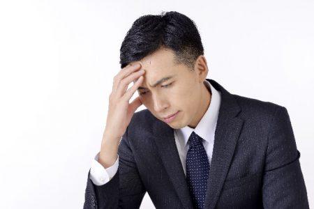 頭を抱える男性のイメージ画像